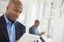 Средний взрослый мужчина в костюме с помощью цифрового планшета на рабочем месте . — стоковое фото