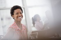 Cheerful woman in pink shirt laughing while sitting at desk in office interior. — Stock Photo