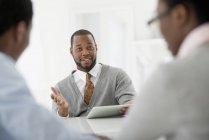 Homme adulte moyen avec tablette numérique assis à la réunion avec couple . — Photo de stock