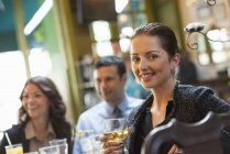 Mid adult woman holding wine and looking in camera while sitting in bar with friends. — Stock Photo