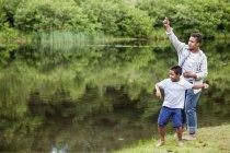 Два брата, бросали камни в воде на берегу озера в лесу — стоковое фото