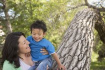 Mother playing with son in park by tall tree trunk. — Stock Photo