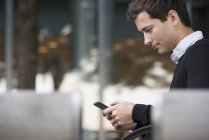 Side view of young man sitting on bench and using smartphone. — Stock Photo