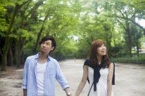 Giovani coppie che tengono le mani sulla data nel parco — Foto stock