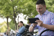 Man using digital tablet on bench in city park with woman talking on phone in background. — Stock Photo