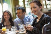 Media mujer adulta manteniendo smartphone y mirando en la cámara mientras está sentado el bar con los amigos - foto de stock