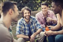 Група веселий друзями чоловічої розвалившись в гамаку в саду і пиття пива. — стокове фото