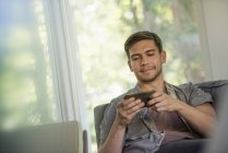 Man sitting on sofa and checking smartphone indoors. — Stock Photo