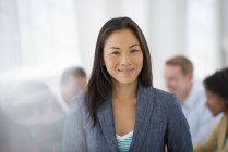 Mujer de negocios de confianza de pie en la sala de reuniones con colegas en segundo plano . - foto de stock
