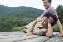 Молода пара розслабляючий на дерев'яні jetty із видом на гірське озеро. — стокове фото