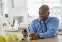 Homem de camisa azul, sentado à mesa do café da manhã com café e usando smartphone. — Fotografia de Stock