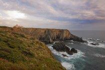 Lighthouse on headland on Atlantic coastline cliff. — Stock Photo