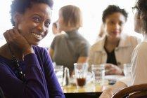 African american mujer sentada con la mano en el mentón en bar con los amigos - foto de stock
