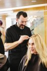 Mature male hairstylist working on client hair and applying hair dye in salon. — Stock Photo
