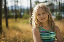Elementary age girl with long blonde hair in woodland by lake. — Stock Photo