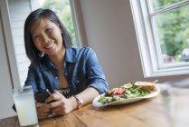 Asiatin mit Smartphone am Tisch bei Kaffee und Salat. — Stockfoto