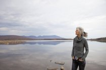 Mature woman looking away on shore of autumnal lake. — Stock Photo