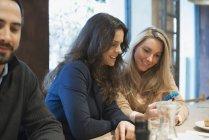 Women sharing smartphone at restaurant table. — Stock Photo