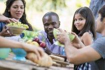 Amis avec la fille d'âge élémentaire assis à la table extérieure dans le jardin avec des fruits et légumes . — Photo de stock