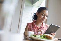 Donna sorridente durante l'utilizzo di tablet digitale al tavolo del caffè con caffè e sandwich . — Foto stock