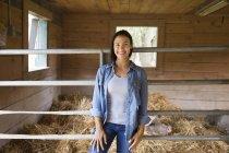 Mulher de pé ao lado de porco em caneta na fazenda . — Fotografia de Stock