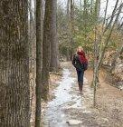 Femme en manteau d'hiver et foulard rouge, marcher dans le chemin dans la forêt hivernale. — Photo de stock