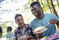Молодий чоловік і хлопчик різання фрукти пиріг на пікніку таблиці — стокове фото