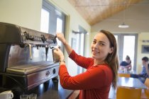Young woman making coffee with large coffee machine. — Stock Photo
