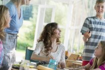 Family cooking at cooking at table on farmhouse terrace. — Stock Photo