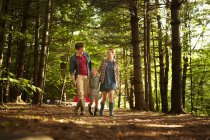 Family with daughter walking in woodland in soft light. — Stock Photo