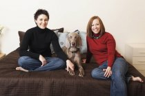 Lesbian couple posing with Weimaraner dog on bed. — Stock Photo