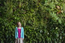 Girl standing in front of wall covered with ferns and climbing plants. — Stock Photo