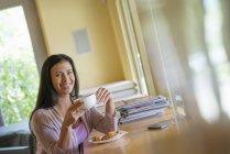Frau bei Kaffee am Tisch mit Smartphone nebenan im Café. — Stockfoto