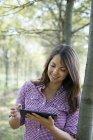 Donna in piedi in Viale degli alberi e utilizza la compressa di digital. — Foto stock