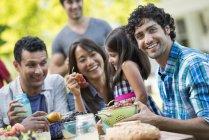 Adultos com menina de idade elementar sentados à mesa com frutas no jardim . — Fotografia de Stock