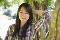 Ritratto di giovane donna in camicia di plaid contro il tronco d'albero — Foto stock
