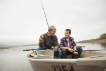 Mature man and teen boy sitting and fishing from boat. — Stock Photo