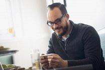 Bärtiger Mann benutzt Smartphone und lächelt im Café. — Stockfoto