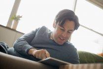 Man at home using digital tablet on sofa. — Stock Photo