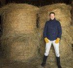 Uomo in posa in fattoria di fronte fieno impilato . — Foto stock