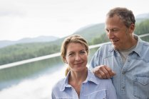 Mature couple standing and posing by lake shore. — Stock Photo