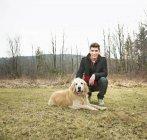 Молода людина гладить золотистий ретрівер собака в осінній ліс. — стокове фото