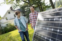 Mid adult man with son walking by solar panel in farmhouse garden. — Stock Photo