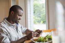 Junger Mann sitzt mit Smartphone im Café am Tisch mit Salatteller. — Stockfoto