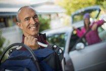 Uomo che tiene la borsa e la donna in piedi dalla portiera della macchina aperta, lasciando per il viaggio. — Foto stock