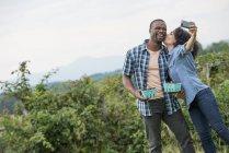Donna che bacia l'uomo mentre prende selfie con smartphone alla fattoria di more . — Foto stock