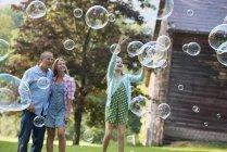 Genitori che guardano figlia prendere bolle di sapone e ridere in campagna . — Foto stock