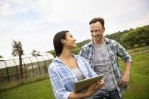 Homem e mulher usando tablet digital na fazenda orgânica . — Fotografia de Stock