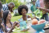 Jóvenes amigos compartiendo platos con comida en la mesa de picnic en el jardín de campo - foto de stock