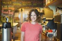 Giovane donna in piedi di macchina per il caffè in caffè — Foto stock